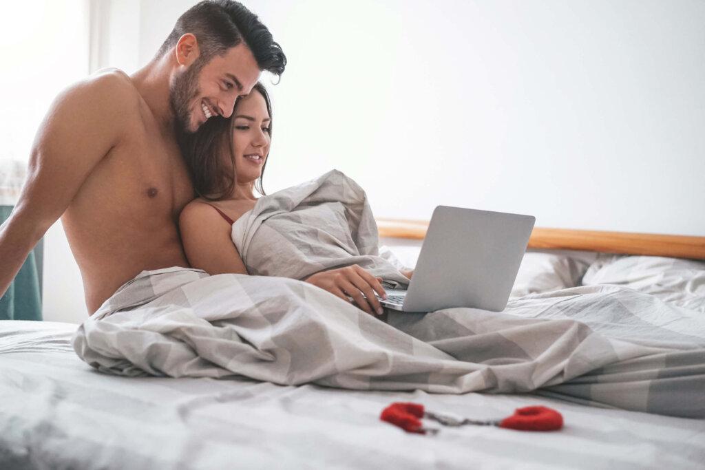 Par sidder i seng og kigger på en computer mens et par røde sexlegetøjshåndjern ligger ved siden af