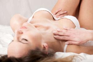 Kvinde ligger i seng iført hvidt lingeri