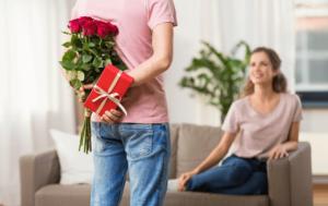 En mand gemmer roser og en gave bag ryggen, mens en kvinder sidder i en sofa og kigger på ham
