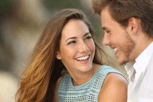 Kvinder med brunt hår smiler imens hun kigger på en mand med skæg