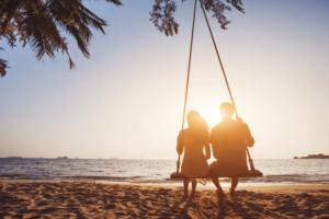 Mand og kvinde sidder på en gynge på en strand og kigger ud på vandet
