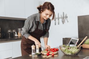 En kvinde står i et køkken og skærer tomater på et skærebræt