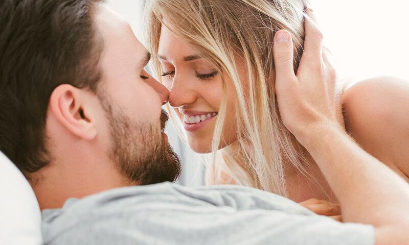Lyshåret kvinder ligger ovenpå en mand med skæg