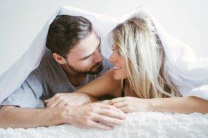 Lyshåret kvinde og mørkhåret mand kigger på hinanden mens de ligger under en dyne i en seng.