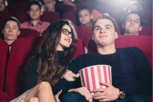 ungt par der sidder i biografen med popcorn